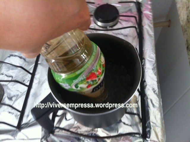 Ferva água numa panela e coloque a garrafa do vinagre (com a tampa lacrada) de ponta cabeça e encoste apenas a tampa na água fervente por 10 segundos.